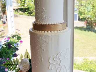 Tall statement cake with white on white handpiped details, lace impressions, and gold