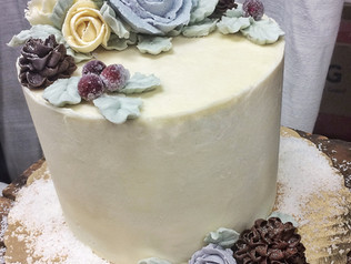 Winter themed cake with hand piped flowers, leaves, and pinecones, and sugared cranberries