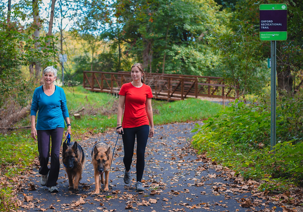 Women walking dogs on Phase 1 of trail