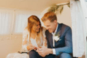 Bride & Groom sit inside kombi booth at their wedding looking at photo strips