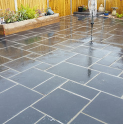 Dark grey patio with sleeper flowerbeds