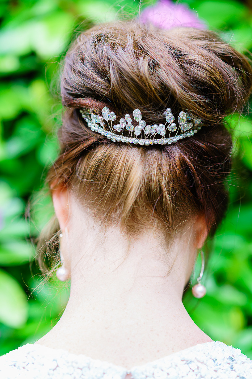 A relaxed up do - a high messy bun encircled with a crystal tiara