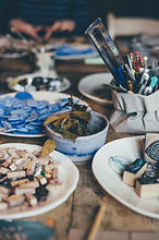 little plates and ceramic bowls holding various art mterials on wood table, such as stamps, leaves, mosaic glass, brushes, photo by annie spratt