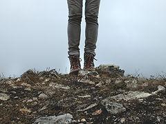 Feet and legs standing on rocky earth, photo by amanda sandlin