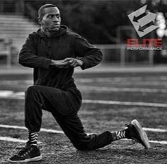 Athlete dynamic stretching outdoors on a football field