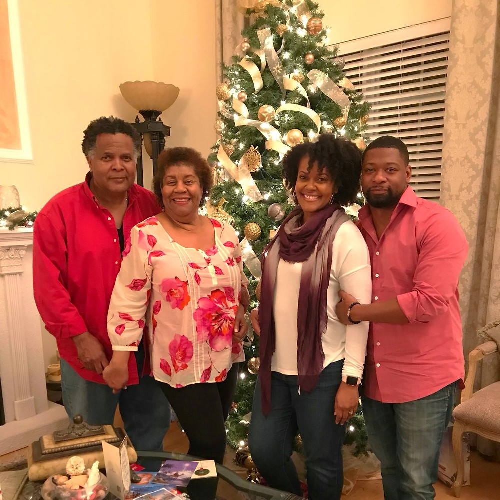 Family photo with my parents, my husband and myself in front of the Christmas tree