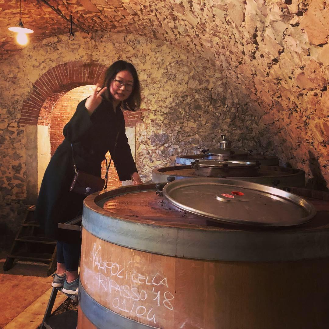 Woman looks into a wine cask