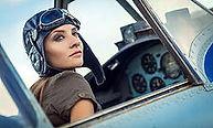 אישה צעירה ויפה עם כובע ומשקפיי טייס יושבת בתא טייס, קוקפיד