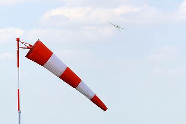 שק רוח בצבעי אדום ולבן מתנפנף ברוח כשברקע טס טיסן על שלט
