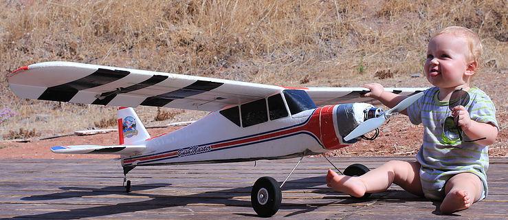 תינוק חמוד עם משקפי טייסים יושב ליד טיסן חשמלימונחה רדיו