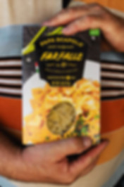 Man holding a packaging of pasta farfalle Papa Scapolo by ZBS BRANDS.