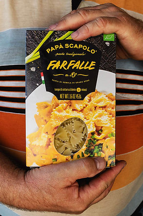 Мужчина держит макароны бабочки Papa Scapolo от брендингового агентства ЗБС БРЭНДС.