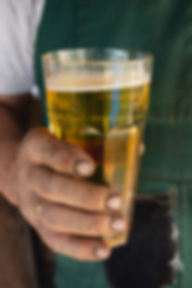 Man holding a glass of beer by Last Incident Brewing Company.