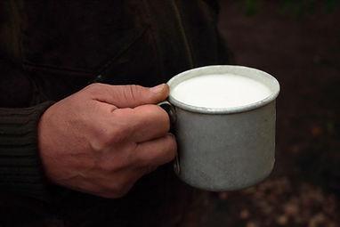 Man holding a cup of ShambaLait milk.