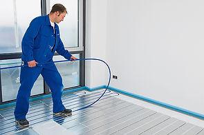 A man installing underfloor heating pipe