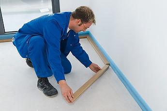 A man installs wooden perimeter battens