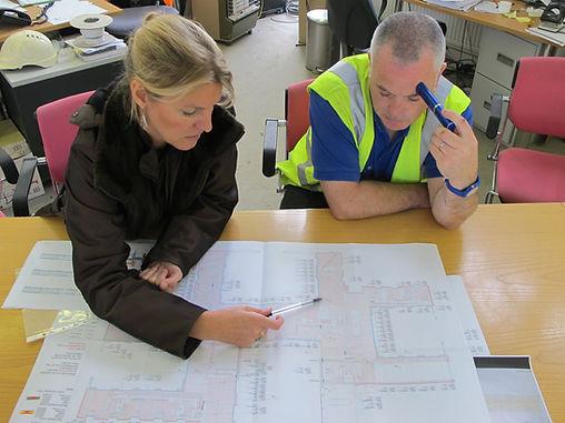 Man an woman study underfloor heating plan