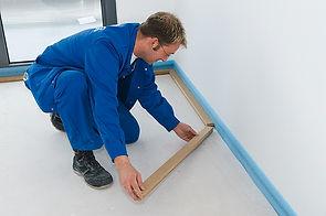 A man installs the perimeter and support battens