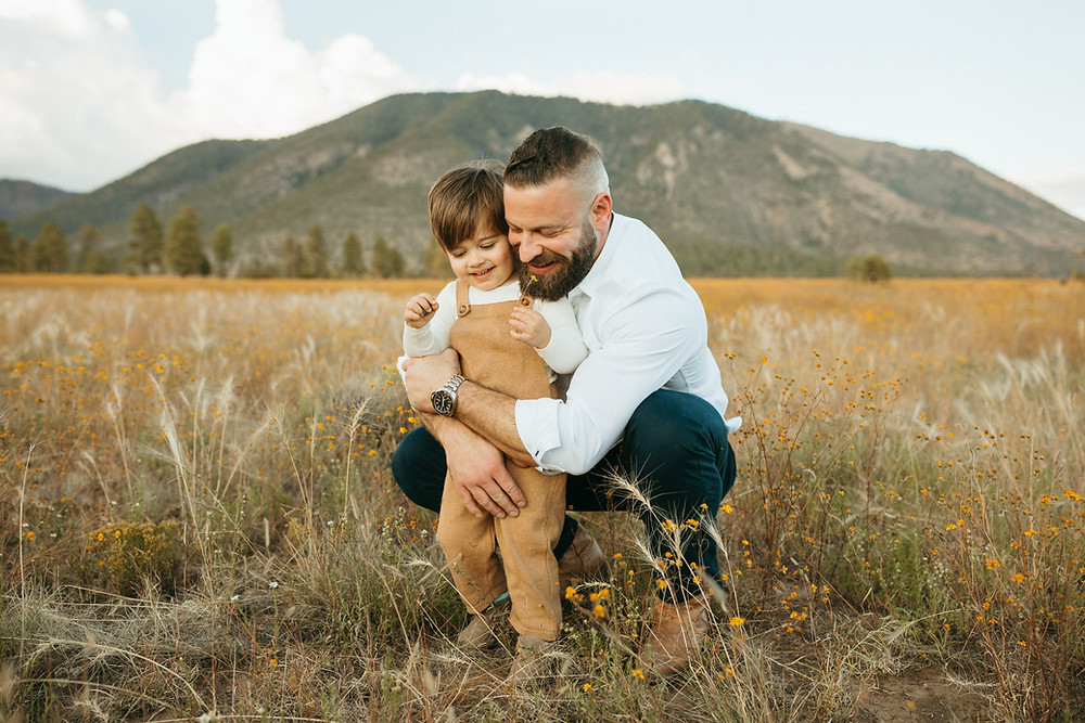 father and son play in Buffalo Park for family photography session