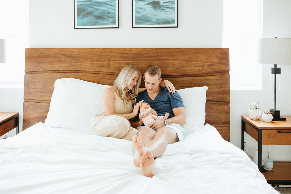 family cuddles baby in Phoenix newborn lifestyle photography session