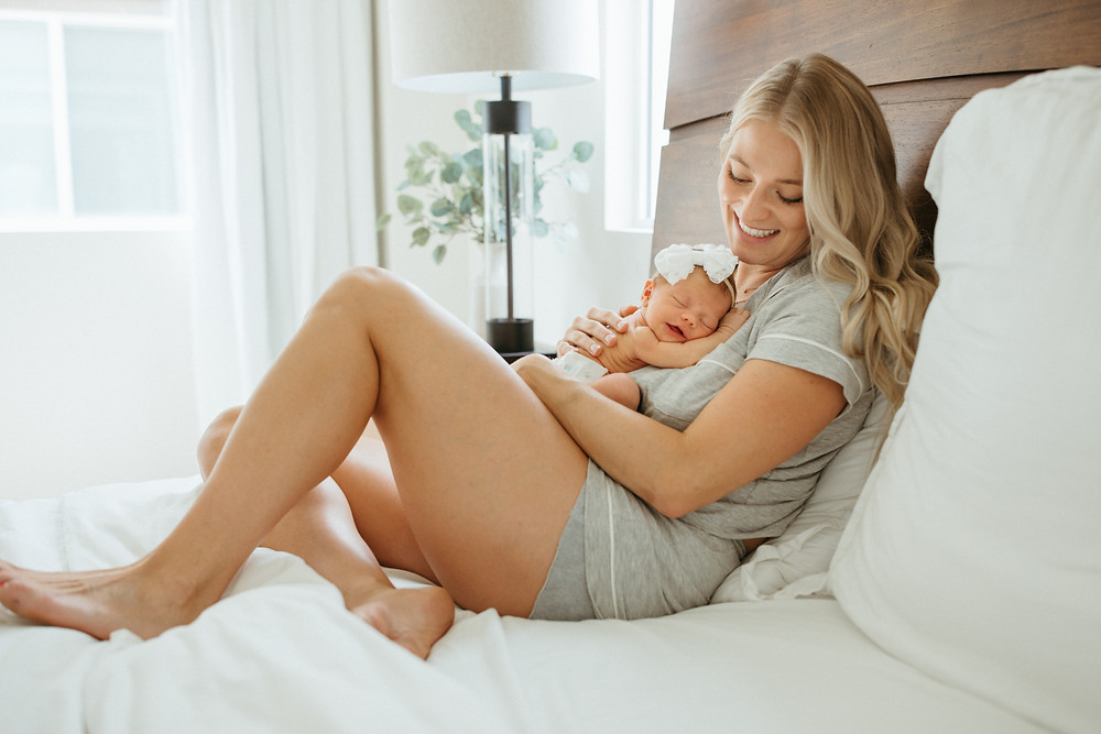 mom cuddles baby for newborn lifestyle photography session in Phoenix