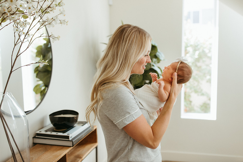 woman holds baby for scottsdale newborn lifestyle photography session