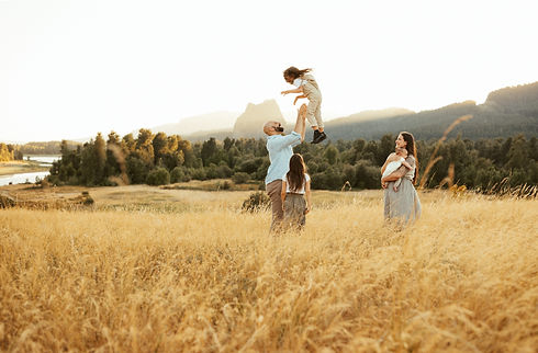 family plays in field for portrait session