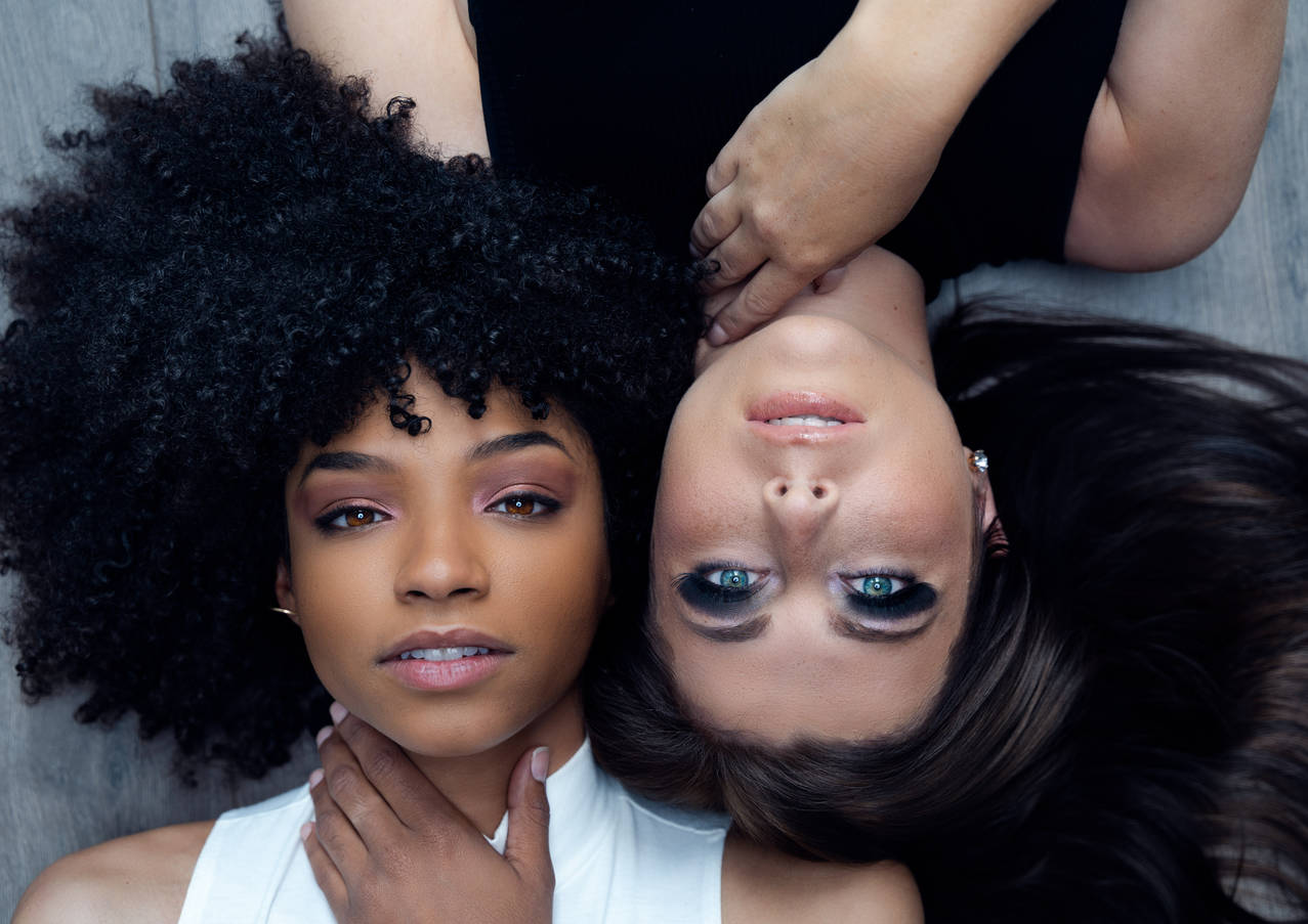 Two woman posing next to each other in a creative portrait