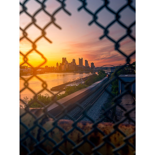 Glowing Orange sunrise from the West End Bridge in Pittsburgh with a train rolling through shot through a hole in the fence