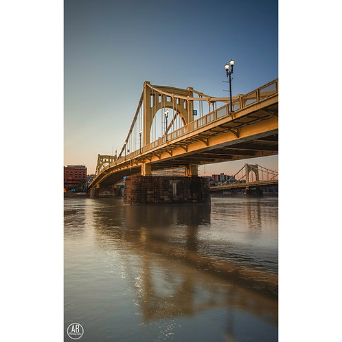 Photo of the Andy Warhol Bridge during a sunset in Pittsburgh featuring reflections.
