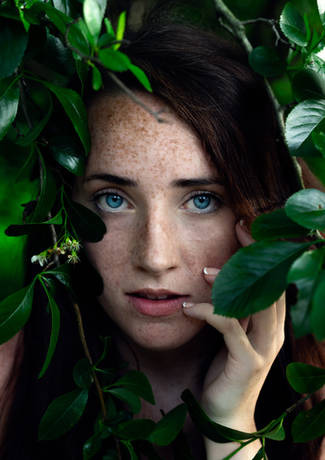 Woman posing for a creative portrait in green bushes