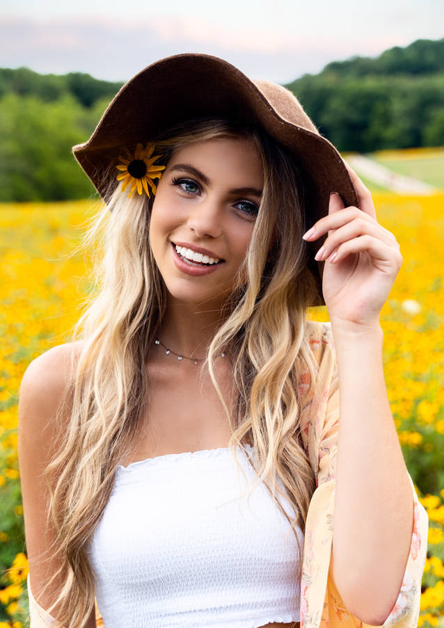 Blonde woman posing for a portrait in a bed of flowers