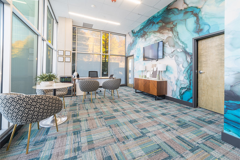 Modern office space featuring floor to ceiling windows, unqiue wall paint and beautiful modern decor