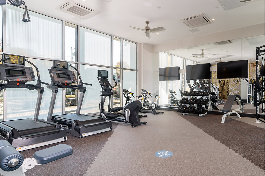 In apartment gym featuring cardio equipement such as treadmills an ellipticals. State of the art gym equipment