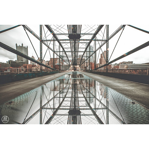 Photo of the Smithfield Bridge located in downtown Pittsburgh with puddle reflection of Pittsburgh skyline.