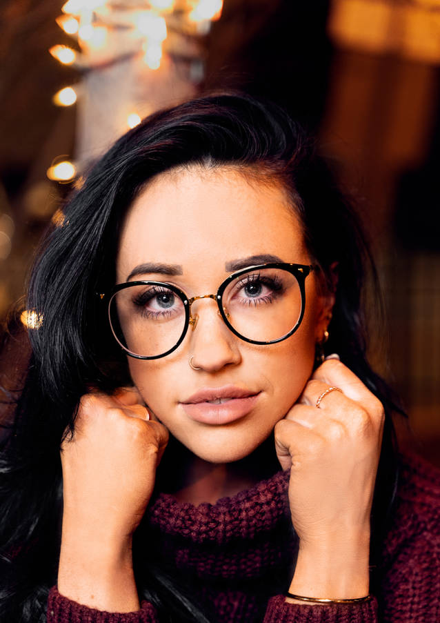female portrait with glasses and warm tones