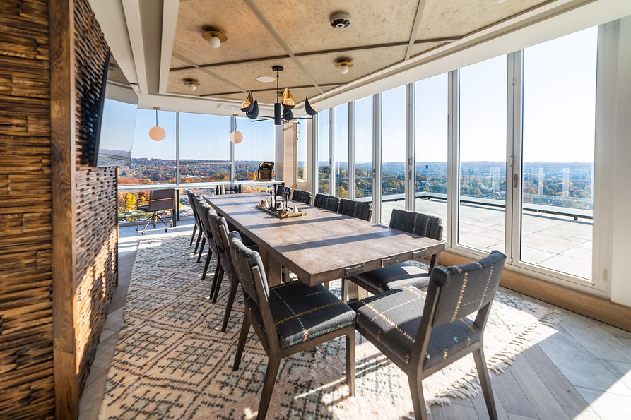 Experience luxury dining at this pent house community area featuring modern dining room furniture, floor to ceiling windows and a beautiful view of Pittsburgh