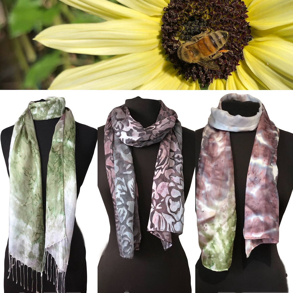A bee gathering pollen on a sunflower, three Joy Hand Painted Silk Scarves draped on body forms