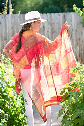 Woman wearing a colorful Hand Painted Silk Ruana, backlit stained glass pattern