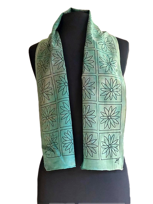 Crepe de chine hand painted silk scarf is festooned with a graphic black daisy motif on a vivid green palette. 8 x 54 inches