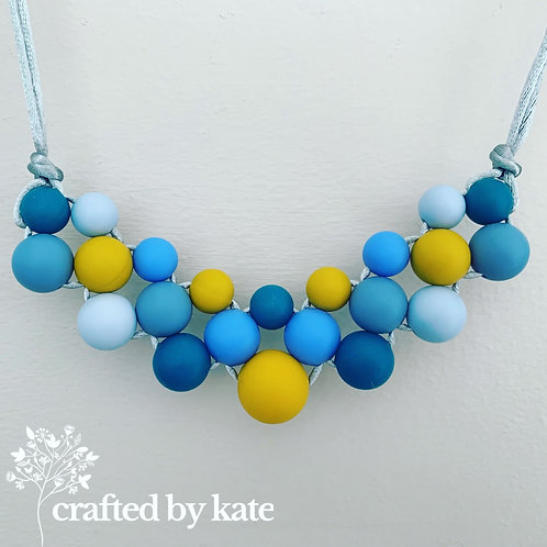 Woven blue and mustard yellow teething necklace