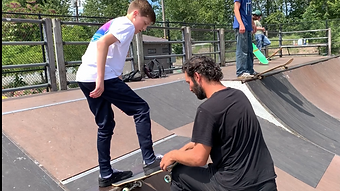 chad caruso teaching a beginner skater how to drop in on skateboard