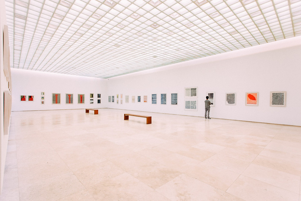 art gallery with bright lights, white walls and colourful artworks on the wall.