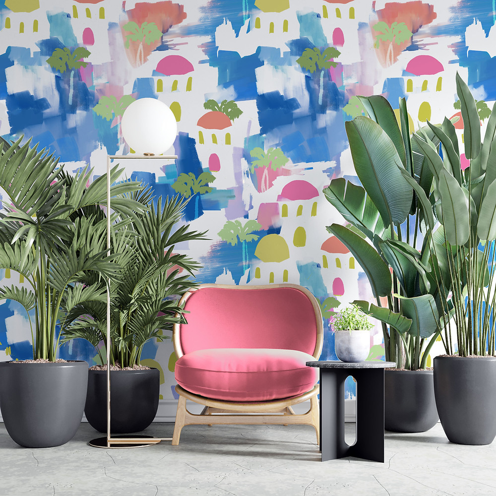 A photo of a room with a pink chair and lots of jungle plants in black pots. The wallpaper is of an abstract scenic painting, with blue brushstrokes in the background and white buildings with yellow and pink rooves, and palm trees.