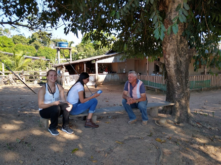 Rachel, a student interviewer, and a farmer sitting on a low bench under a tree.