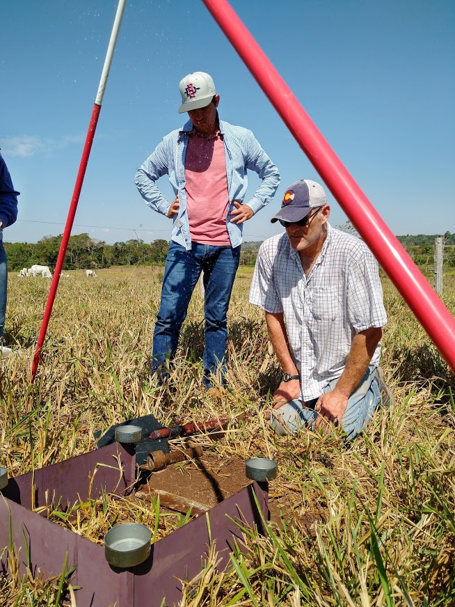 Trent Biggs kneels in a pasture looking at a rainfall simulator set up on the ground. Cleiton Cavalheiro stands next to him, hands on his hips.