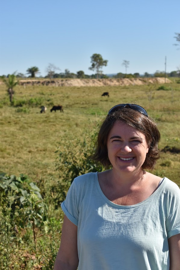 Katrina Mullan standing in front of a pasture with cows