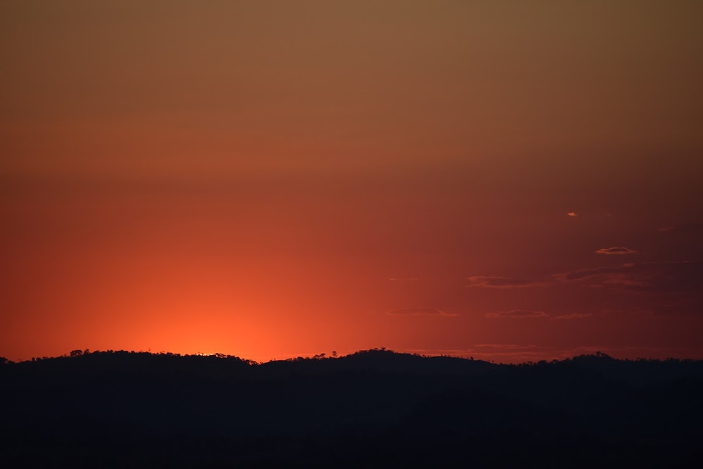 red sky over dark shadowed hills at sunset
