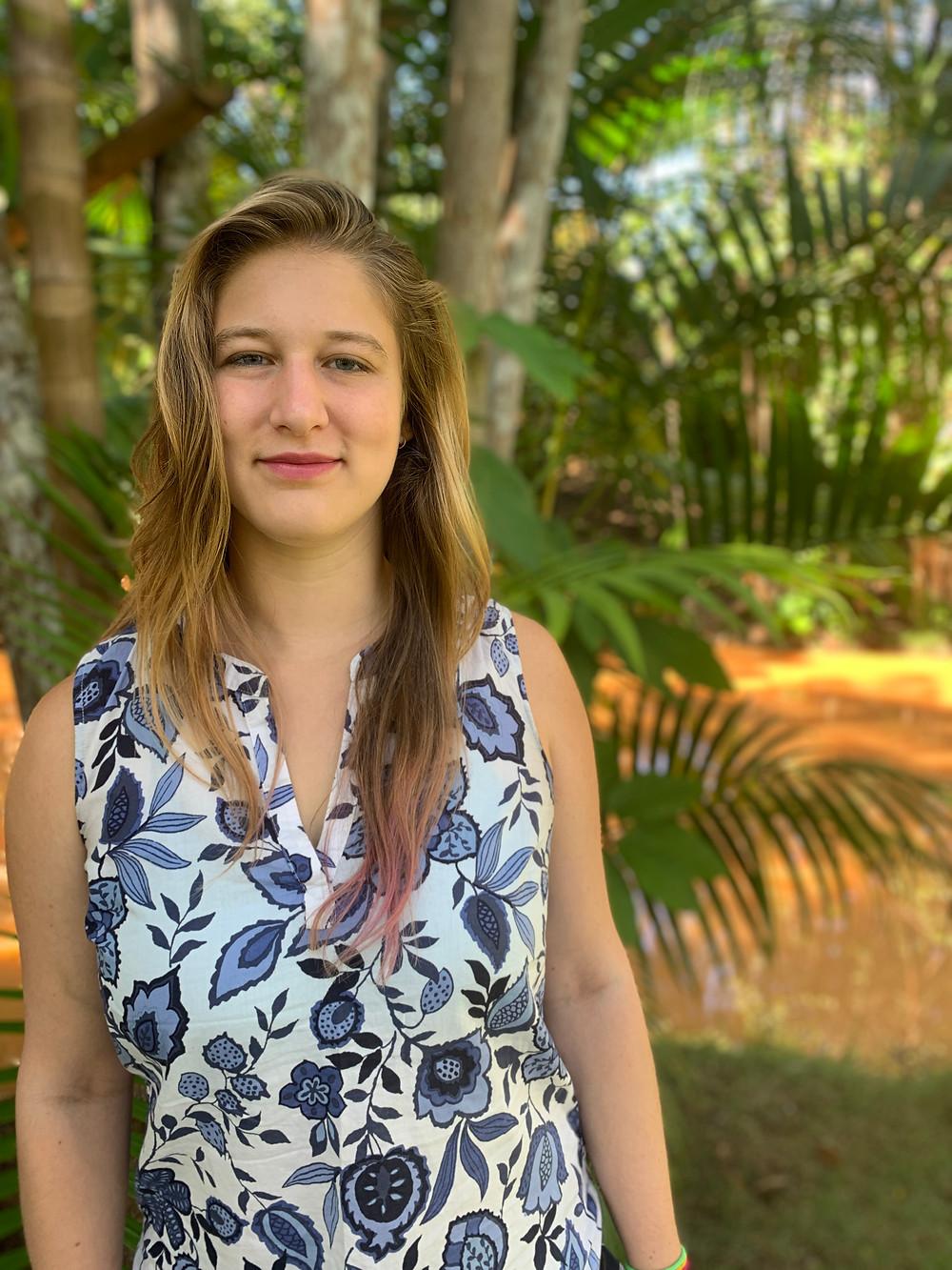 Retrato de Cassie Sevigny com folhas de palmeira ao fundo.