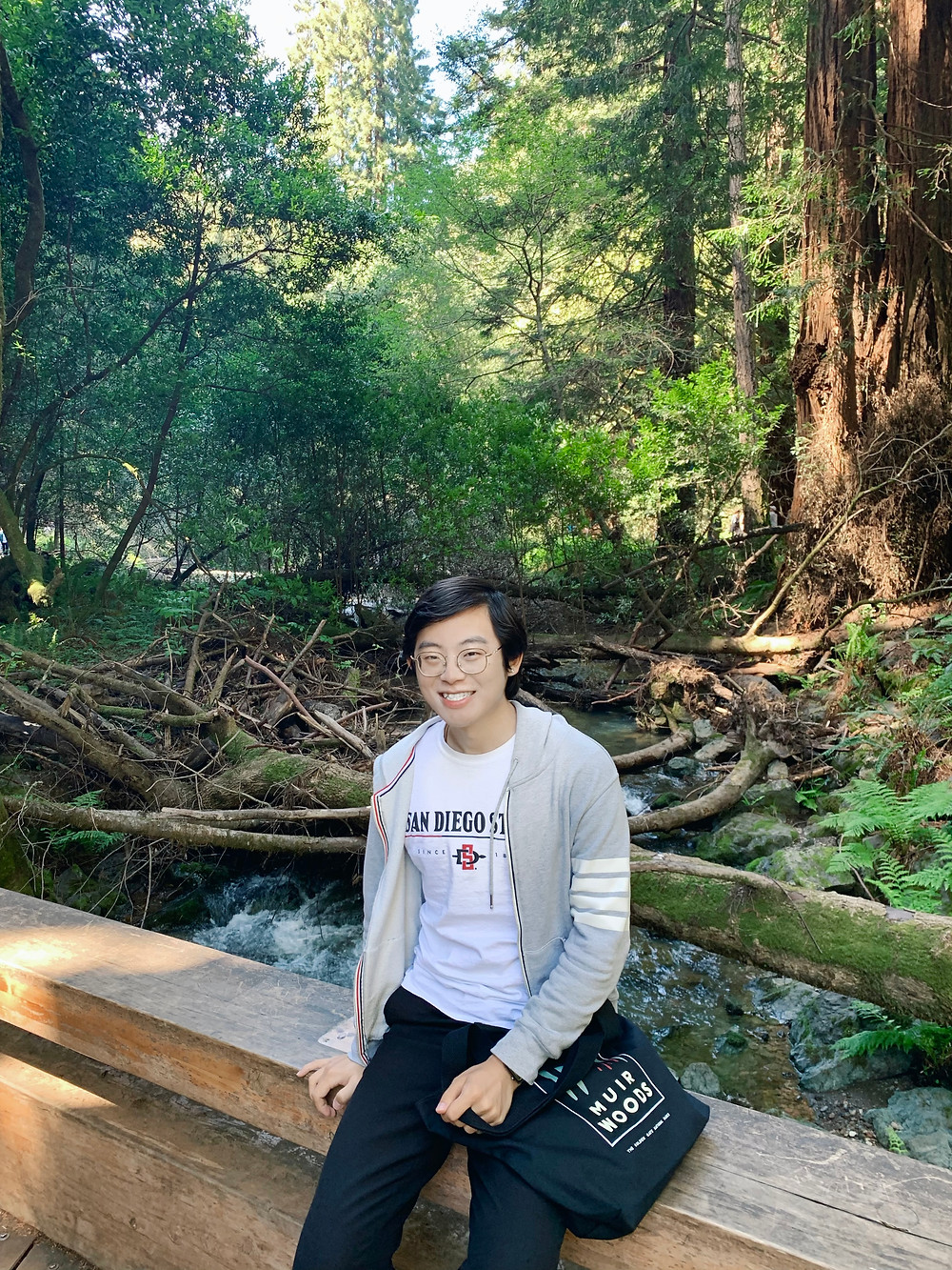 Ye Mu sitting on a wooden railing of a bridge over a creek in a forest.
